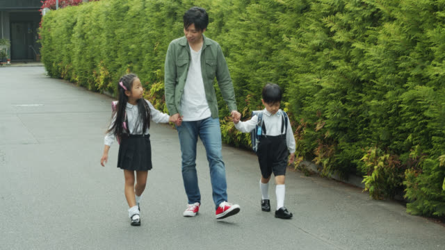 Young Japanese Father Walking Children to School