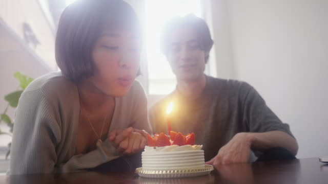 クリスマスにイチゴのスポンジケーキにろうそくを吹く若い日本の女性 - birthday点の映像素材/bロール