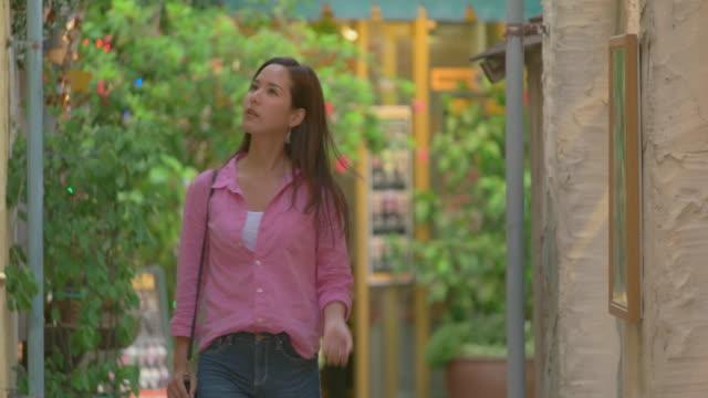 vídeos de stock e filmes b-roll de young japanese female enjoy window shopping. - ver montras