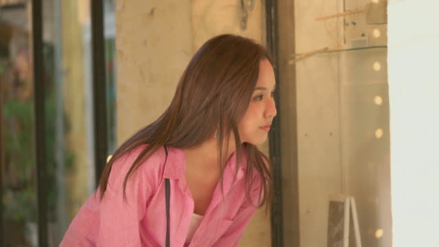 vídeos de stock, filmes e b-roll de young japanese female enjoy window shopping. - olhando vitrines