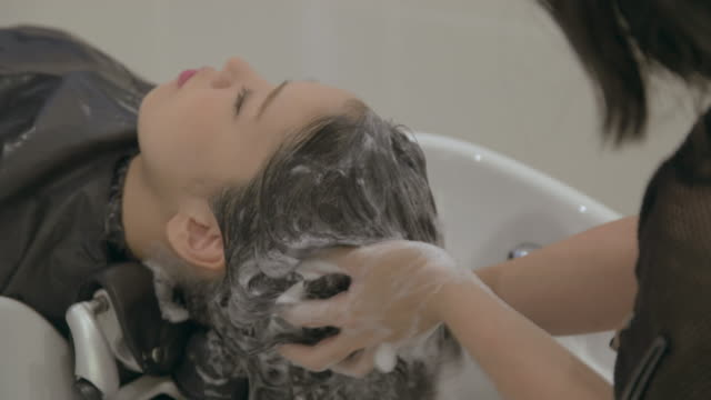 young japanese female in a hair salon. - shampoo per capelli video stock e b–roll