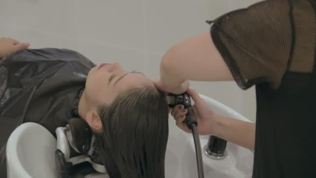 young japanese female in a hair salon. - kopf nach hinten stock-videos und b-roll-filmmaterial