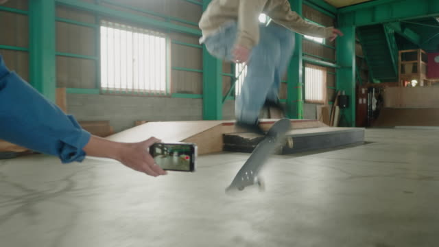 Young Japanese female skateboarder taking video on smartphone of her friend performing tricks