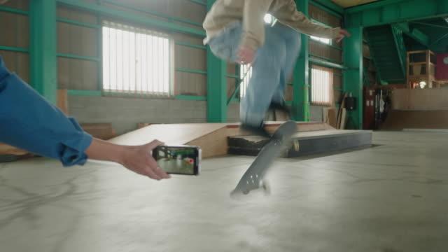vidéos et rushes de jeune skateboarder féminin japonais prenant la vidéo sur le smartphone de son ami exécutant des tours - filmer