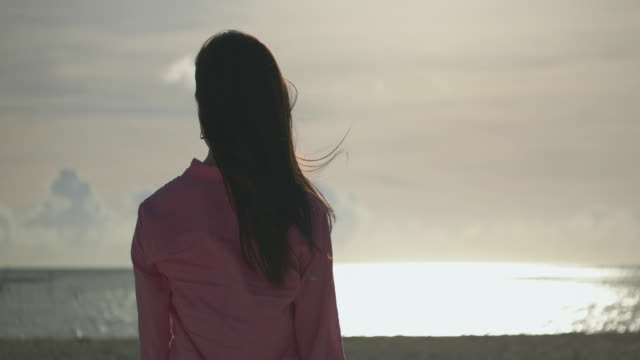 young japanese female standing and looking ocean. - 後ろ姿点の映像素材/bロール