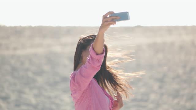 young japanese female taking selfie on the beach. - 撮影テーマ点の映像素材/bロール