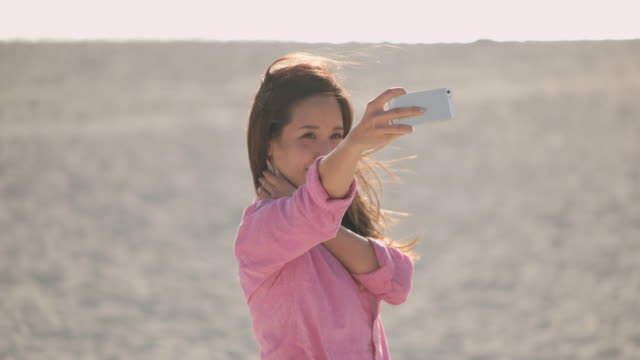 Young Japanese female taking Selfie on the beach.