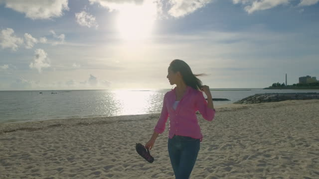 Young Japanese female walking on the beach at sundet.