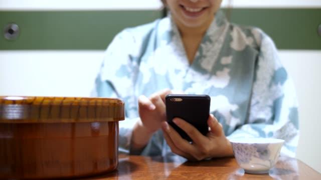 young japanese girl using phone - yukata video stock e b–roll