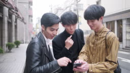 Young Japanese Male Friends Checking Map Online in Urban Tokyo