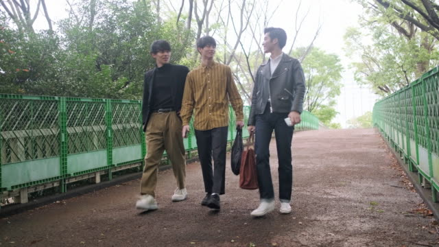 young japanese male friends walking in tokyo park - city break stock videos & royalty-free footage