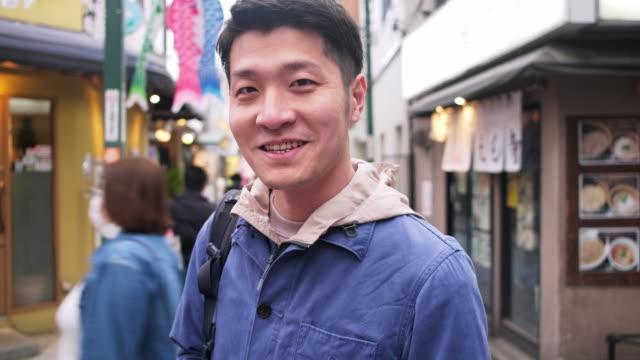 夕暮れ時に東京を探索する若い日本人男性旅行者 - looking at camera点の映像素材/bロール