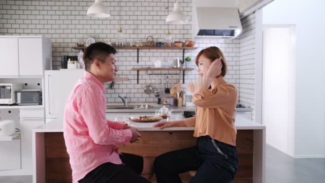 お茶でキッチンでくつろぐ若い日本人男性と妻 - 向かい合わせ点の映像素材/bロール