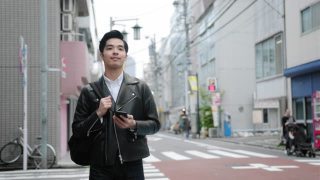 young japanese man in casual clothing crossing tokyo street - leather jacket stock videos & royalty-free footage