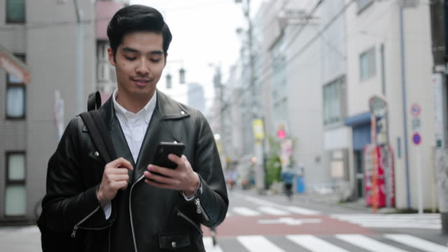 young japanese man in casual clothing crossing tokyo street - striding stock videos & royalty-free footage