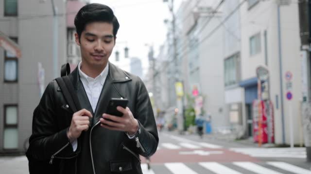 vídeos y material grabado en eventos de stock de joven japonés en ropa casual cruzando la calle tokio - paso largo