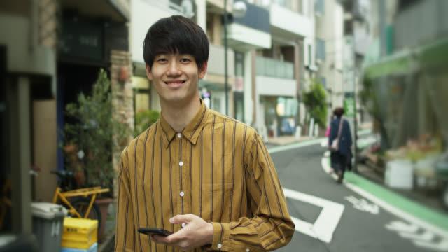 携帯電話から見上げてカメラに微笑む日本の若者 - ハンサム点の映像素材/bロール