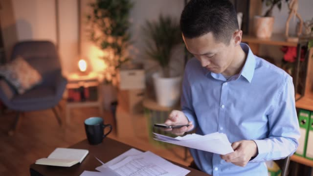 young japanese man paying bills online - electronic banking stock videos and b-roll footage