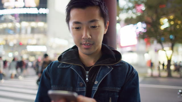 cu a young japanese man using a mobile phone at shibuya crossing / tokyo, japan - 男性一人点の映像素材/bロール