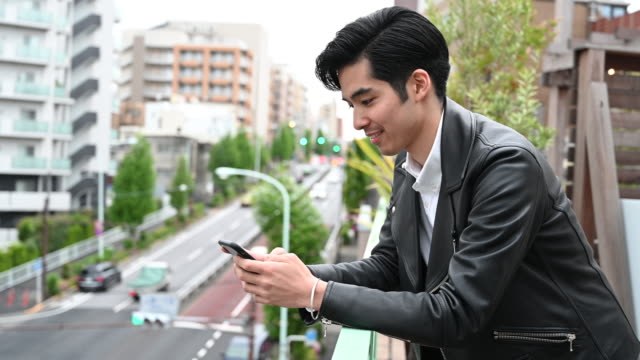 young japanese man using smart phone then looking up - waist up stock videos & royalty-free footage