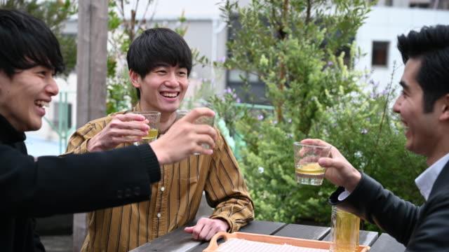 日本の若い男性が眼鏡をかけて乾杯し合う - パティオ点の映像素材/bロール