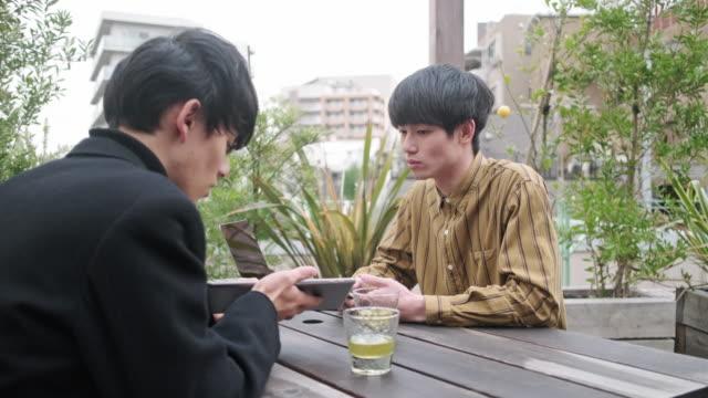アウトドアでお茶と技術を楽しむ若い日本人男性 - casual clothing点の映像素材/bロール