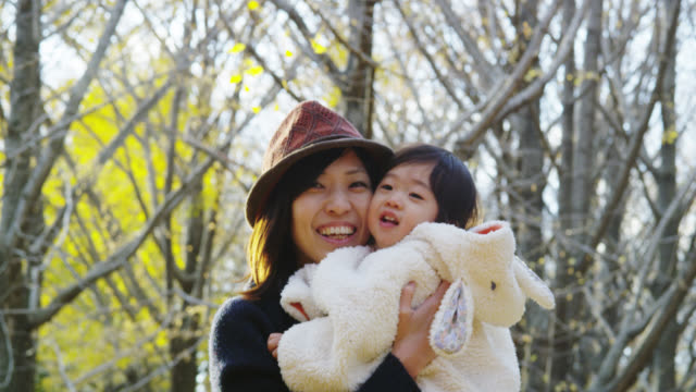 Young Japanese Mother having fun with her 1 1/2 year old daughter in the Park