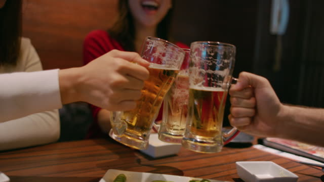 CU Young Japanese people raise beer glasses in a toast / Tokyo, Japan