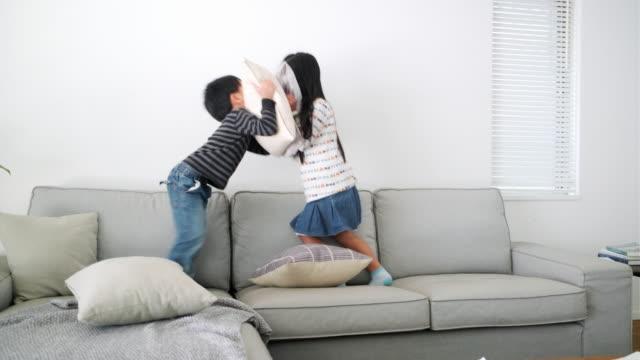 ソファで枕の戦いをする若い日本の兄弟 - 兄弟点の映像素材/bロール