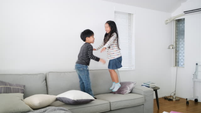 若い日本の兄弟がソファでジャンプして遊ぶ - 兄弟点の映像素材/bロール