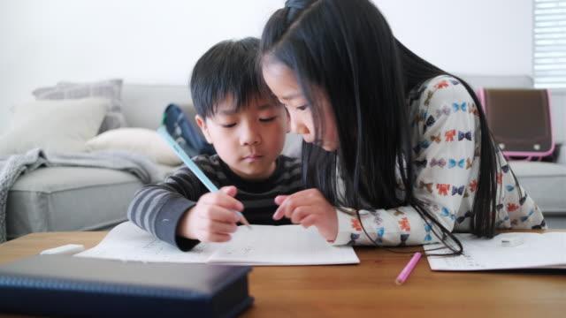 日本の若い姉妹が弟の宿題を手伝う - 鉛筆点の映像素材/bロール