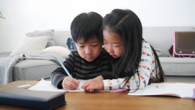 日本の若い姉妹が弟の宿題を手伝う - 兄弟点の映像素材/bロール