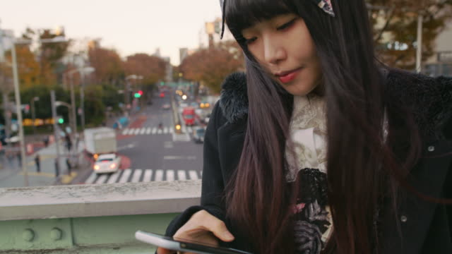 A young Japanese woman checks her phone in Harajuku / Tokyo, Japan
