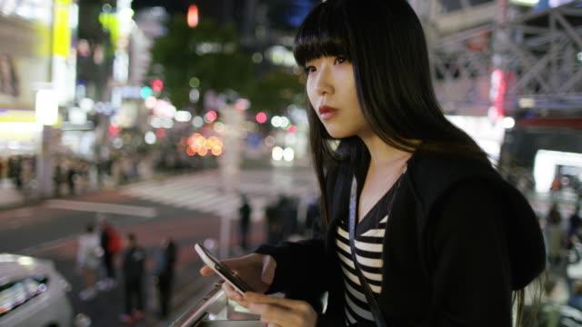 ms a young japanese woman checks her phone in shibuya / tokyo, japan - 心配する点の映像素材/bロール