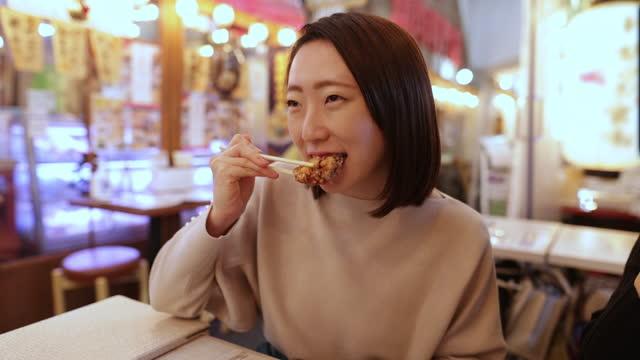 stockvideo's en b-roll-footage met jonge japanse vrouw die gebraden kip in staaf izakaya eet - voorgerecht