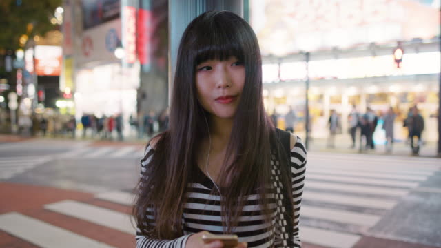 vidéos et rushes de ms a young japanese woman listens to music and checks her phone / tokyo, japan - cheveux raides