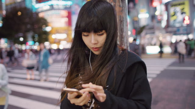 vidéos et rushes de ms a young japanese woman listens to music and checks her phone / tokyo, japan - la vingtaine