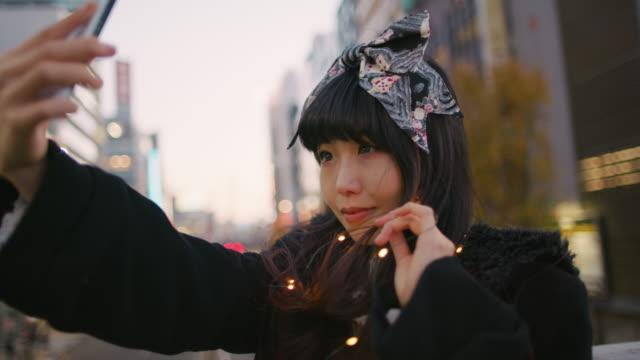 A young Japanese woman takes selfies in Harajuku / Tokyo, Japan