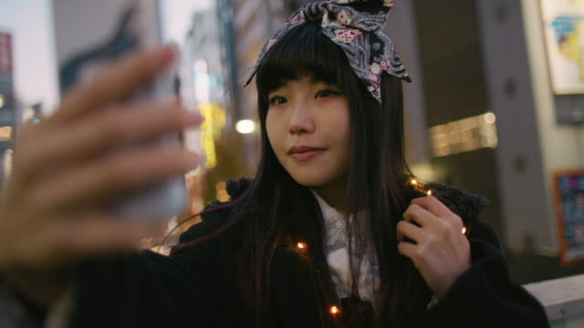 stockvideo's en b-roll-footage met a young japanese woman takes selfies in harajuku / tokyo, japan - zelfportret fotograferen