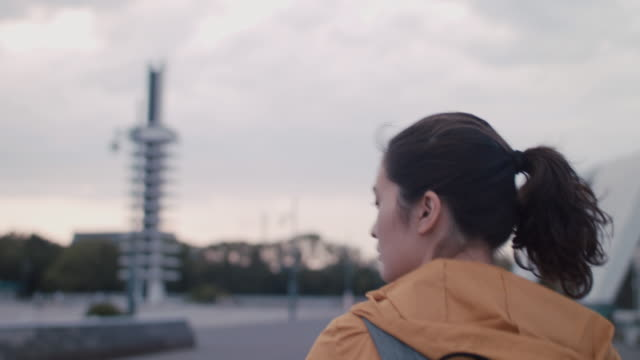 stockvideo's en b-roll-footage met young japanese woman walking with backpack and headphones  in tokyo, japan. - bovenlichaam