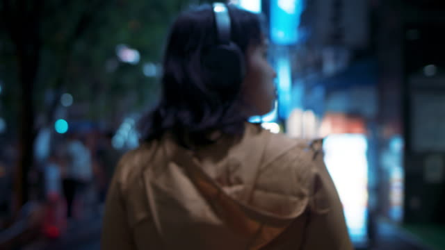 vídeos y material grabado en eventos de stock de young japanese woman with hooded jacket and headphones walking at night in tokyo, japan - vista posterior