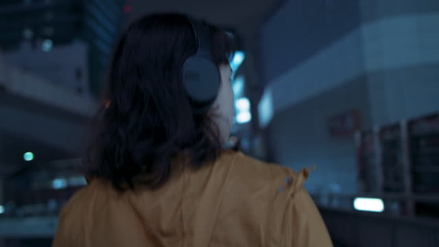young japanese woman with hooded jacket and headphones walking at night in tokyo, japan - back lit bildbanksvideor och videomaterial från bakom kulisserna
