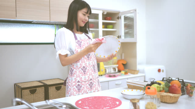 young japanese woman working at a kitchen - stereotypical homemaker stock videos & royalty-free footage