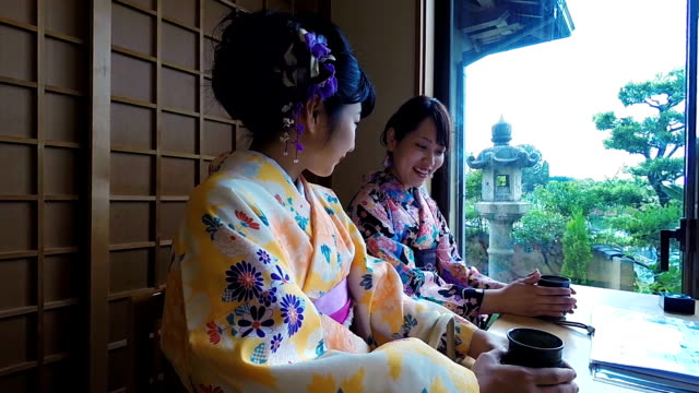 young japanese women drinking tea while wearing traditional kimonos - gion stock videos and b-roll footage