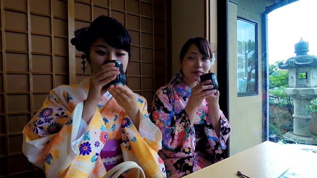 vídeos y material grabado en eventos de stock de mujeres japonesas jóvenes beber té mientras visten kimonos tradicionales - sado