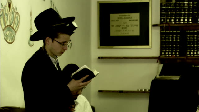 a young jewish man reads from the torah. available in hd. - torah stock videos and b-roll footage