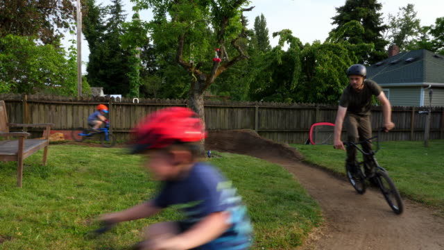 ms young kids and father riding bmx bikes on backyard dirt track on summer afternoon - bmx stock-videos und b-roll-filmmaterial