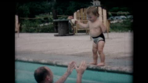 vidéos et rushes de 1958 young kids learning to jump into pool - film d'amateur