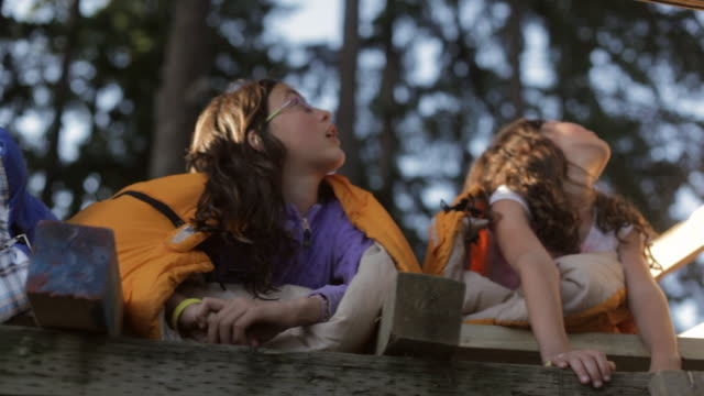 LA Young kids lying in a tree fort looking out into the sky / Vancouver, British Columbia, Canada
