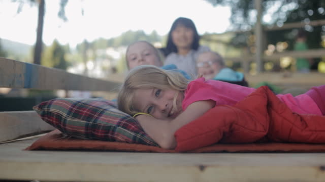 ha young kids lying in a tree fort on their sleeping bags / vancouver, british columbia, canada - 寝袋点の映像素材/bロール